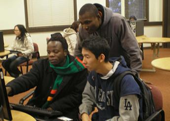 Francis Phiri with friends in front of a computer at the library.