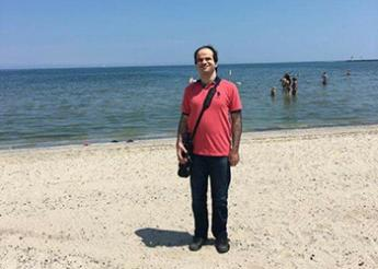 Sameh standing on a beach with the ocean in the background.