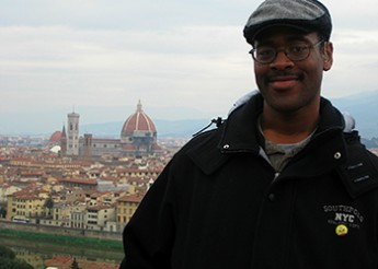 Joseph standing on platform overlooking scenic view of cathedrals and old Italian buildings.