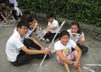 Ming sitting on ground with group of Chinese students with white sticks around them.
