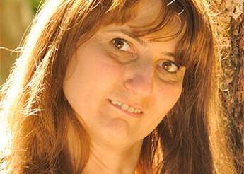 Headshot of Karine, a woman with a disability, smiling at the camera