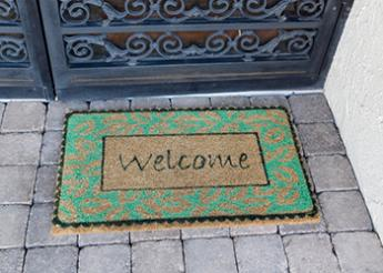 """green welcome mat that reads """"Welcome"""""""