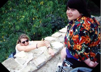 Person reaching up over stone wall to wheelchair user above