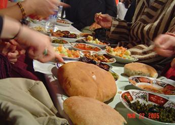 Hands of people around a table full of bread and other food and drink