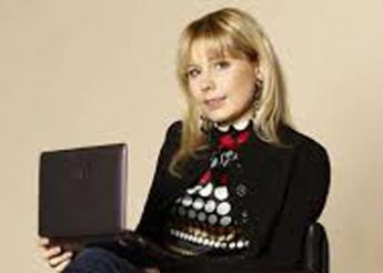 Yulia holds a laptop computer, smiles at the camera