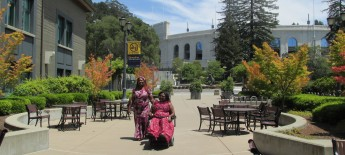 Two women stroll through a university campus surrounded by buildings; one woman uses a power wheelchair and the other walks beside her.