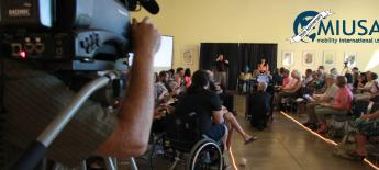 View of a large event space filled with people watching two presenters; in the foreground, a videographer points his camera towards the presenters