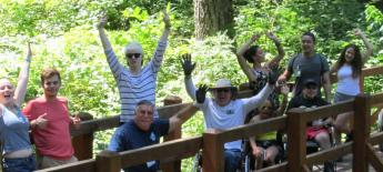 A group of kids with disabilities cheering on a bridge in a forest