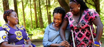 Three women laugh and hug in an outdoor setting. Two wear colorful traditional clothing from their countries in Sub-Saharan Africa.