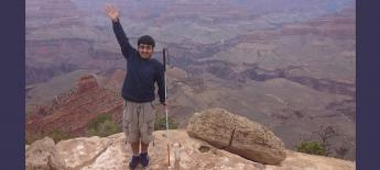 International student who is blind standing on top of the Grand Canyon smiling with white cane in his hand.