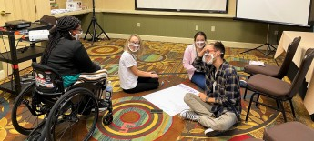 In a conference room, exchange students sit on the floor as they work together on a large sheet of paper, pausing to speak to a staff person who uses a wheelchair.