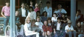 Grainy group photo of 20+ young men and women gathered, wearing 80s/90s-era clothing.