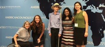5 people smile for camera in front of world map, including one woman who a wheelchair user and a young man wearing a hat and holding a white cane.