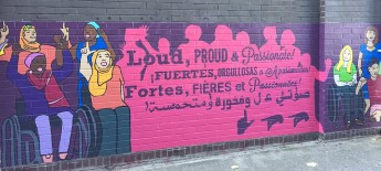 """Close up of portion of mural which shows two small groups of disabled women cheering on either side of a hot pink portion with dark purple text that says """"Loud Proud and Passionate"""" in multiple languages"""