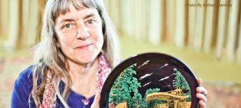 Photo of Susan Sygall holding a decorative plate