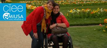 Two women, one standing and one in a wheelchair, in a park; CIEE and MIUSA logo