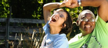 Two women gleefully lock arms and laugh