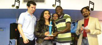 Adriana standing with friends receiving an award for a talent show.