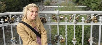 Anne is seated on a bridge covered in thousands of locks.