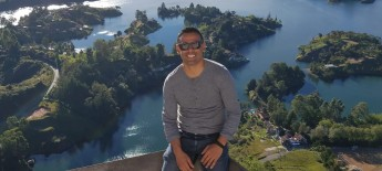 Anthony sits on a ledge, wearing sunglasses, overlooking green islands over water.