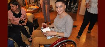 A young woman using a bright red wheelchair smiles at the camera.