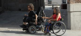 A young woman using a manual wheelchair hangs onto the back of a young man's power wheelchair as he pulls her along a street.
