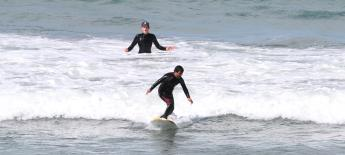 Erdem standing in a surf board with trainer behind him with surprised face.