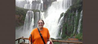 Emily smiling while standing in front of large waterfall holding her white cane.