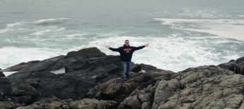 Distant view of a man standing on oceanside boulders with arms outstretched