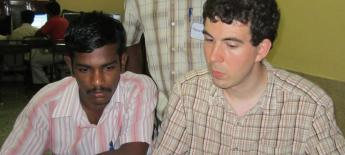 Robert Thompson and two Indian men look at a video on a laptop