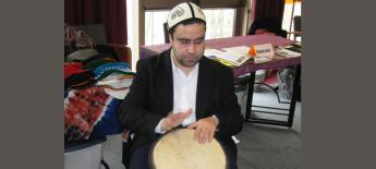Mohammed playing the drums wearing a traditional hat.
