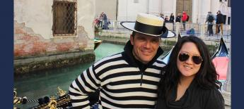 Sheila standing with a gondolier guide in front of canal in Venice with a gondolier in the background.