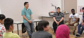 An ESL class sits in a circle with the teacher at front.