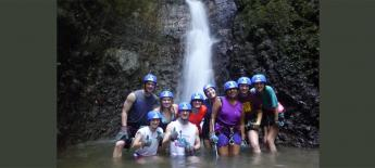 Juanita standing under waterfall with friends.