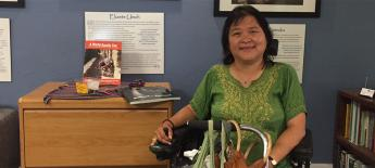 Jeanette, seated in a power wheelchair, at the MIUSA office.