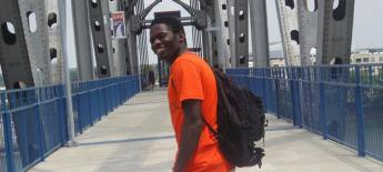 Samson, wearing a bright orange shirt, poses for a picture in front of a bridge.