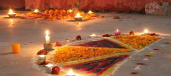 In India, a beautiful scene of colors and candles is assembled on the ground.