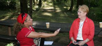 A woman in a red suitcoat listens intently to another woman talking