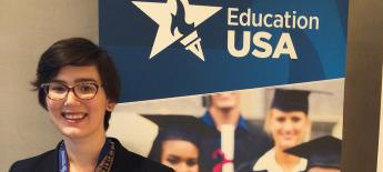 Molly Roza stands in front of an EducationUSA banner.
