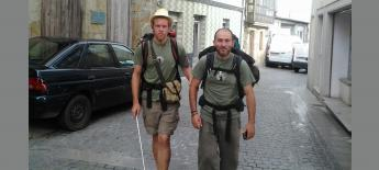 Nick walks with cane and his friend through narrow street in Spain.