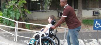 Pushing woman in wheelchair up a ramp.