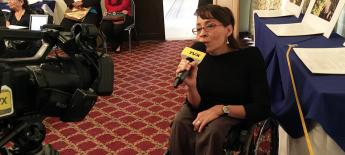 A women using a wheelchair speaks into a microphone in front of a TV camera.
