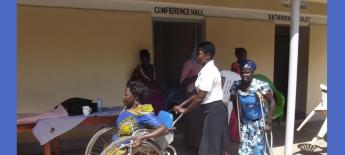 South Sudan women, including one in a wheelchair and one with crutches, come outside from a conference room