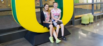 Two students sit in a giant letter U with a rock climbing wall behind them.