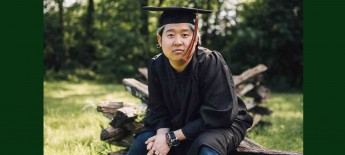 Close up of a young man of southeast Asian origin wearing graduation cap and gown and sitting in forested setting. He wears a neutral expression.