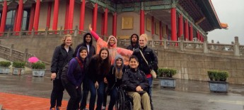 A group of male and female students, including a man seated in a power wheelchair, gather in front of a Chinese monumen in the rain.
