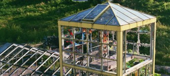 Tall greenhouse-like structure with a shallow pyramid roof