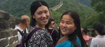 Two women (one is Hannah) look over their shoulders smiling. Great Wall of China is visible behind them.