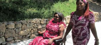 An African woman with a disability and her personal assistant walking.