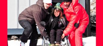 Two men on each side lift the frame of Susan's wheelchair up a short step